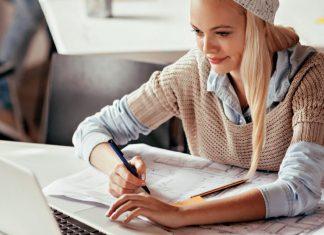 Junge Frau sitzt am Schreibtisch mit Laptop und Stift und Papier.