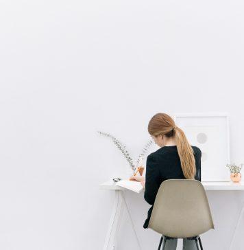 Eine junge Frau sitzt an ihrem Schreibtisch und arbeitet.