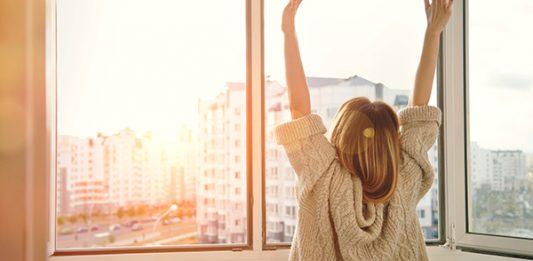 Frau an sonnigen Morgen streckt Hände in die Höhe.