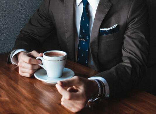 Mann im Anzug sitzt am Tisch mit einer Tasse Kaffee.