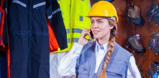 Frau beim Telefonieren mit Sicherheitshelm.