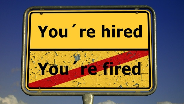 """Schild """"You're hired / durchgestrichenes You're fired"""""""