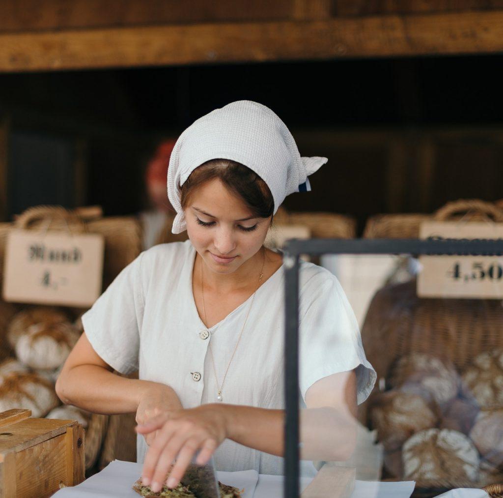 Frau schneidet Brot Arbeitskleidung
