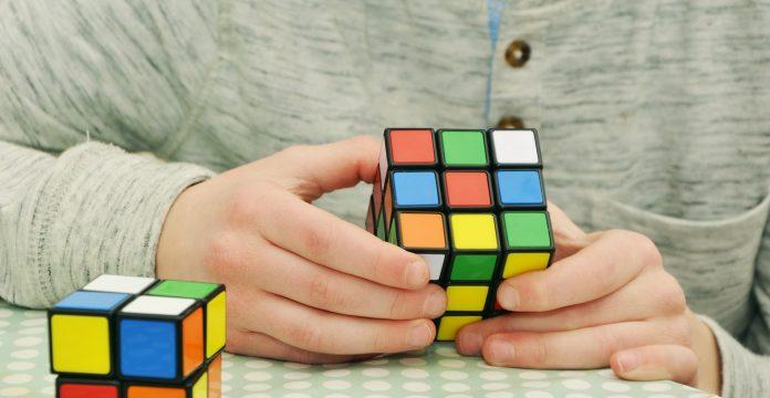 Ein junger Mann löst einen Rubik's Cube.